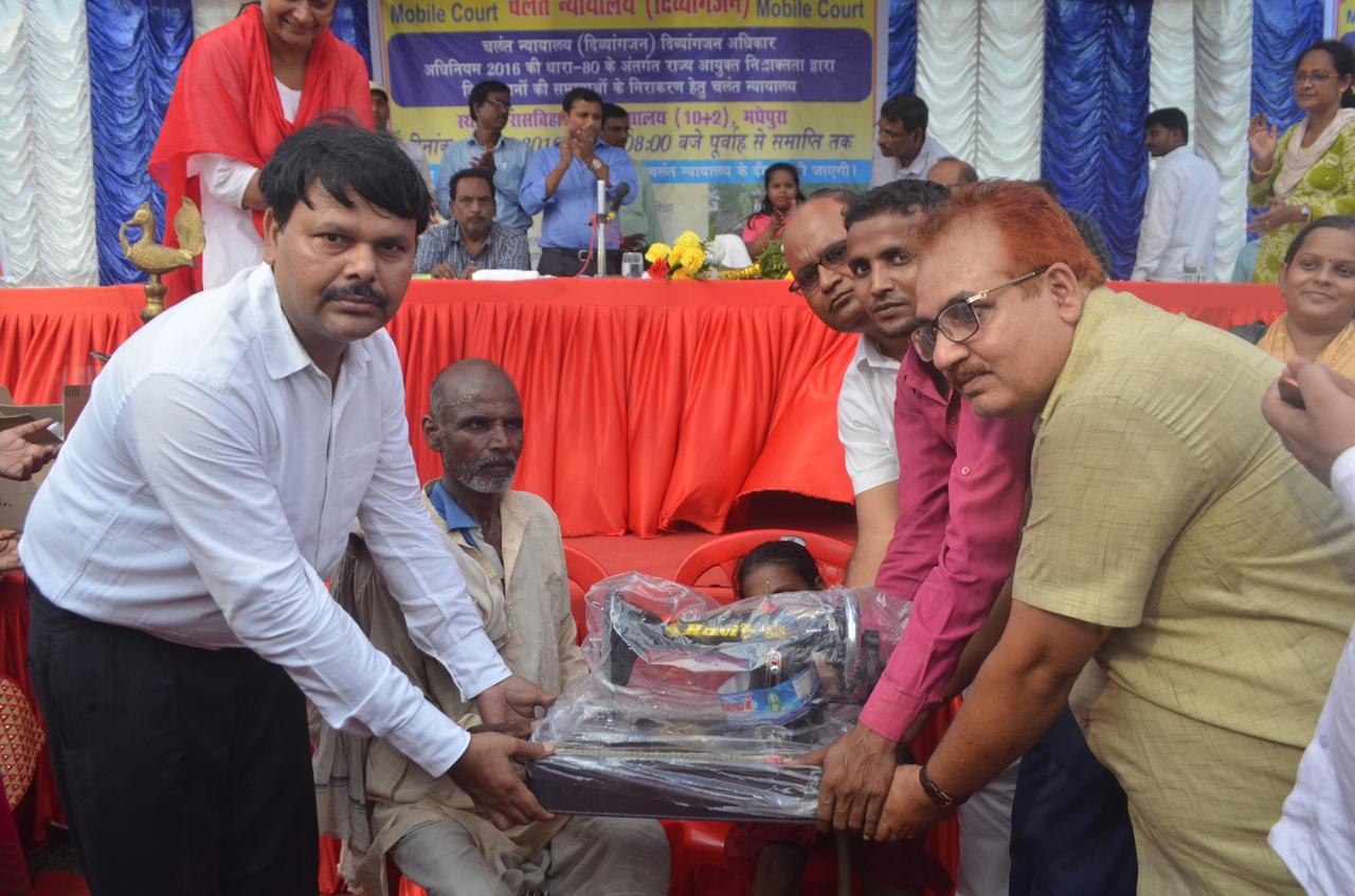 State Disability Commissioner Dr.Shivajee Kumar, Lead Bank Officer Ranjan Kumar Jha (Donor) & others giving a Hand Sewing Portable Machine to a disable girl under eighteen years.